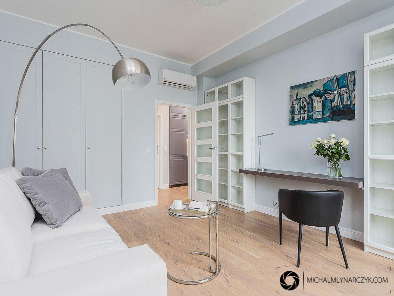 biale biuro z drewniana podloga i czarnym fotelem